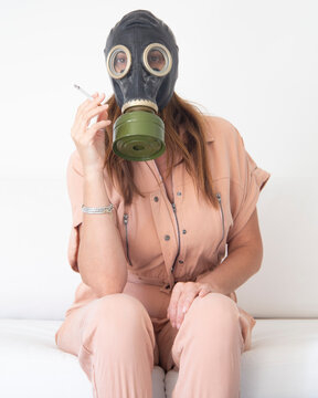 Portrait Of Woman Wearing Gas Mask Holding Cigarette Against Wall