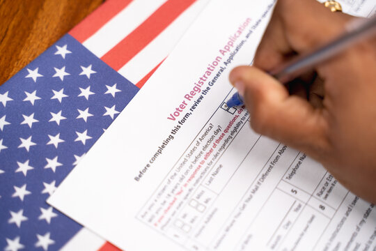 Maski, India - 23, June 2020 : Close up of hands filling President voter Registration Application with US flag as background for upcoming election.