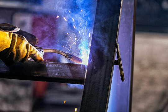The welder is welding a structural steel with gas metal arc welding ( GMAW ) in the workshop.