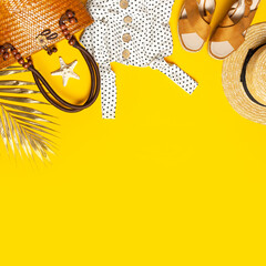 Summer background Beach accessories. Beach wicker straw or rattan women's eco bag white dress straw hat sandals golden tropical leaf on yellow background Flat lay top view copy space Concept of travel
