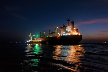 Night loading big mother sea bulk carrier ship with Bauxite aluminium ore from the mini bulk carrier (feeder) vessel at offshore Kamsar port, Guinea, West Africa.