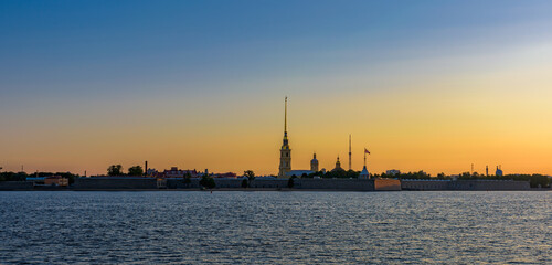 Sunrise panorama of Petropavlovskaya (Peter and Paul) fortress and orthodox Peter and Paul Cathedral on Zayachy Island after summer white night. Saint-Petersburg, Russia
