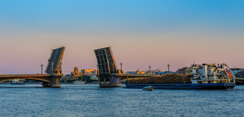 General cargo ship with raw wood logs on deck underway on Neva river at summer sunrise.