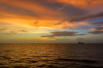 Incredible sunset over sea with a silhouette of a cargo vessel.