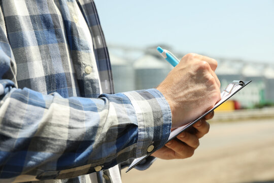 Young man with clipboard and pen against grain silos. Agriculture business