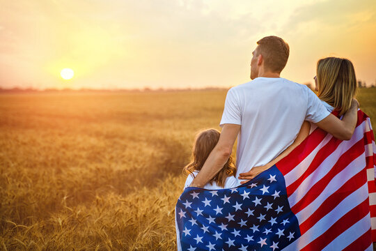 Back view of a unrecognizable Happy family in wheat field with USA, american flag on back.
