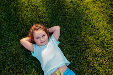 Happy Child girl lying on green grass in summer park. Little girl smiles and looks at the camera....