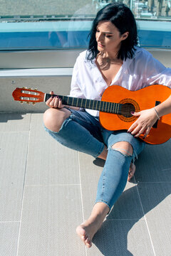 Beautiful Woman Playing Guitar While Sitting On Tiled Floor Outdoors