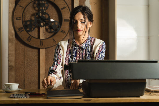 Front view on caucasian woman in vintage office and dress working - Beautiful adult female in 30s sitting by the desk in old fashioned office taking files from table - mystery nostalgia time concept