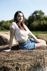 Thoughtful Teenage Girl Sitting On Hay Bale Against Clear Sky