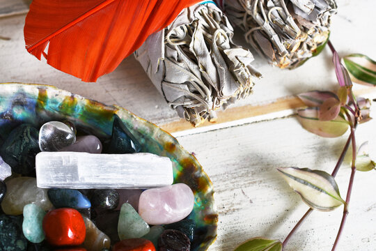 An image of several tumbled healing crystals in an abalone shell with white sage bundles and sacred feather.