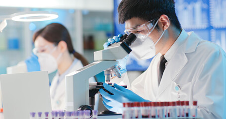man scientist use microscope