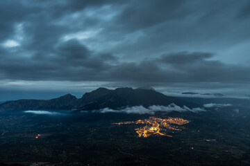 Fotomurales - Scenic View Of Illuminated City Of Oliena Against The Mount Corrasi At Dusk