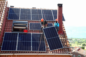 Kauahou and Navarro, workers of the installation company Alromar, set up solar panels on the roof of a home in Colmenar Viejo