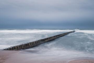 falochron na brzegu morza. Morze Bałtyckie plaża na wschód od Darłowa
