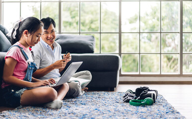 Father and asian kid little girl learning and looking at laptop computer making homework studying...