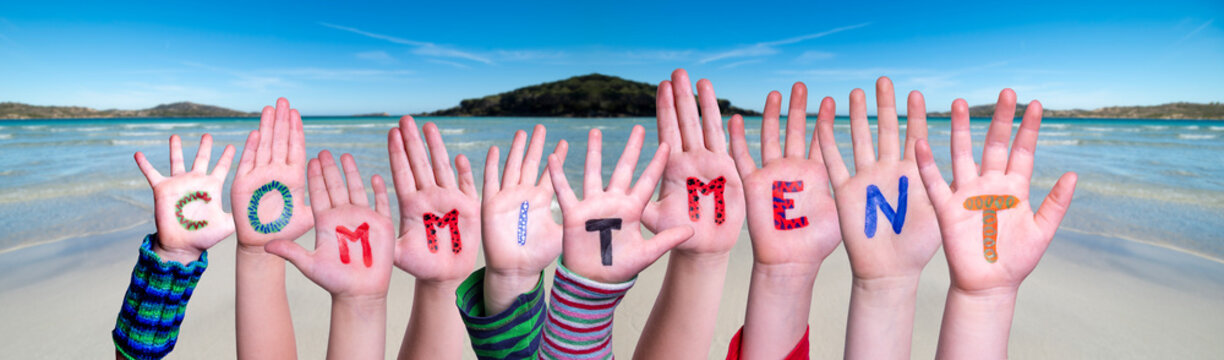 Children Hands Building Colorful Word Commitment. Ocean And Beach As Background