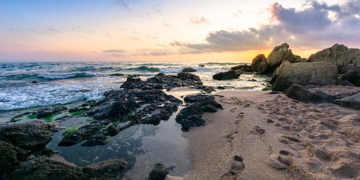 idyllic sunset on the ocean shore. waves crashing rocks on sandy beach. beautiful cloudscape above the horizon