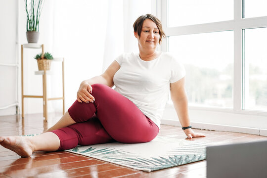 Adult charming brunette woman plus size body positive practice yoga with laptop at the home