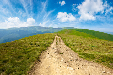 mountain road through grassy meadow. wonderful summer adventure. clouds on the blue sky