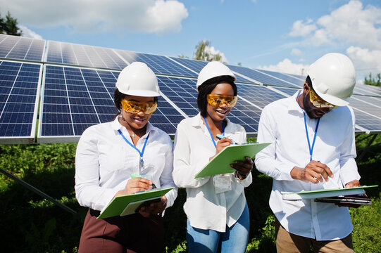 African american technician checks the maintenance of the solar panels. Group of three black engineers meeting at solar station.