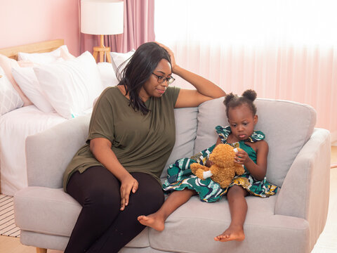 An African American mother was sitting and watching her daughter enjoying a teddy bear on the sofa in the bedroom.