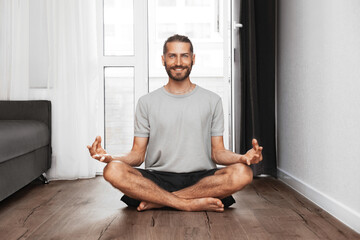 A young man is meditating at home. Man sitting on the floor in lotus position and smiling