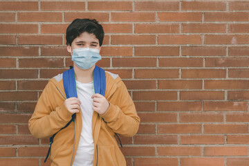 Happy kid with medical mask and backpack going to school