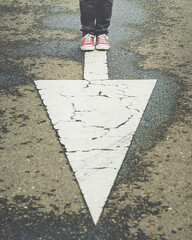 sneakers near the arrow marking of the road