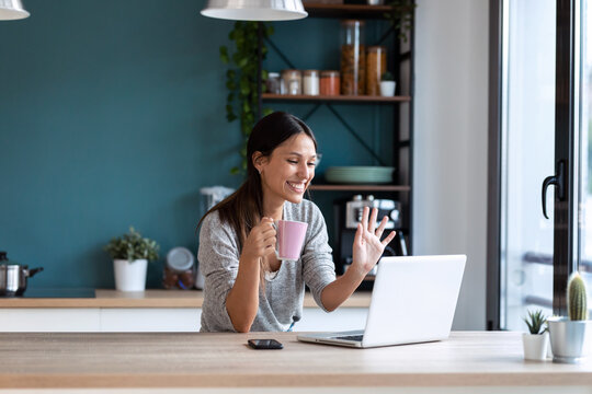 Smiling young woman waving through the laptop web camera while holding a cup of coffee in the kitchen at home.