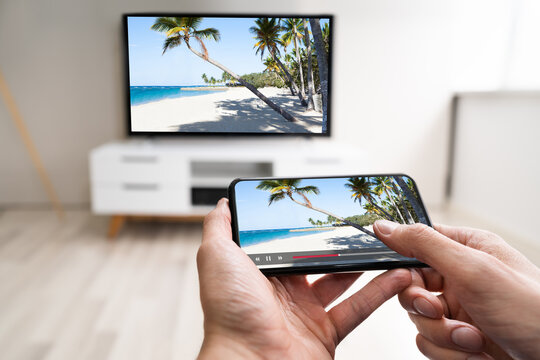 Man Watching TV Streaming From Smartphone