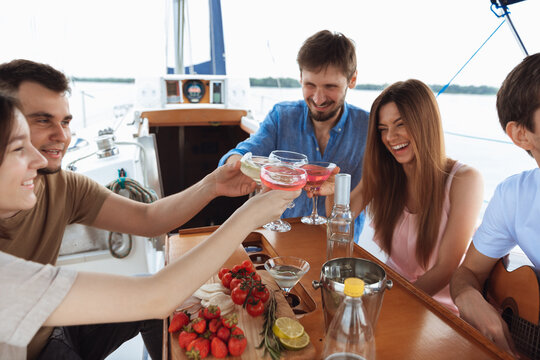 Group of happy friends drinking vodka cocktails at boat party outdoor, cheerful and happy. Young people having fun in sea tour, youth and summer vacation concept. Alcohol, vacation, resting.