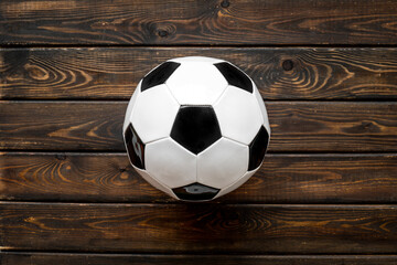 Football ball on wooden background top view copy space