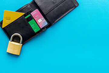 Credit card data security concept with lock on blue desk top view copy space