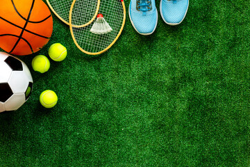 Sport games equipment - balls, sneakers, rockets - on grass top view copy space