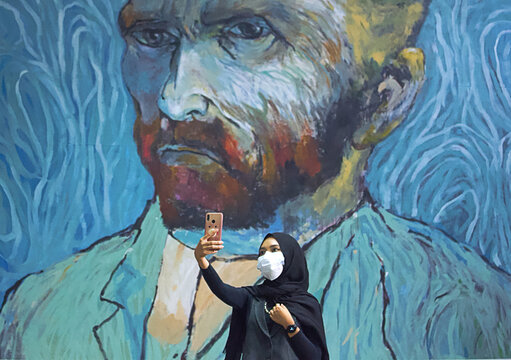 A visitor wearing a protective face mask takes a selfie near an art-wall painted by Indonesian artist Hanafi at Kertas Gallery during an exhibition in Depok