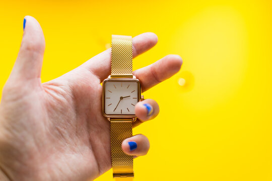 Woman's hand holding a gold watch. Blue painted nails. Copy Space on yellow background