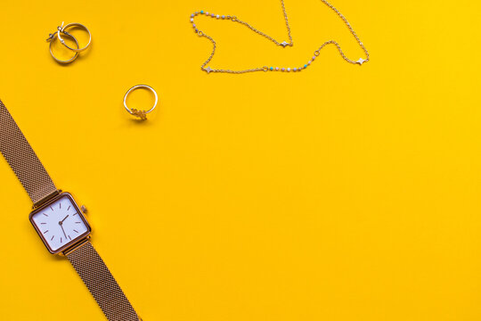 Gold jewelry, earrings, ring, necklace and watch on a yellow background. Copy space.