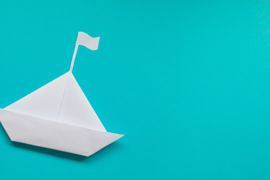 White paper ship on blue background. Copy space.
