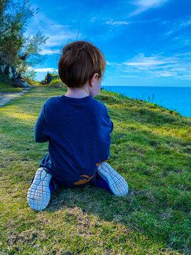 Rear View Of Boy Sitting On Field Against Sky