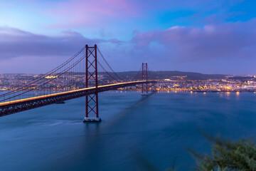 Suspension Bridge In City At Dusk