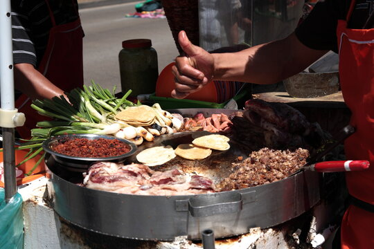 Street Food rich Tacos with toppings and thumbs up in downtown Mexico city