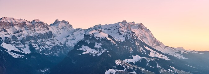 Photo sur Plexiglas Bleu nuit Beautiful scenery of a range of high rocky mountains covered with snow at sunset