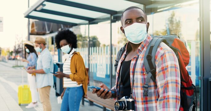 Mixed-races young males and females people im medical masks standing in line at bus stop. Keeping safe social distance. African American stylish man tourist outdoor waiting for transport. Tourists.