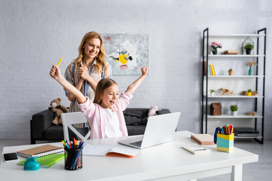 Smiling woman standing near happy child showing yeah gesture during online education