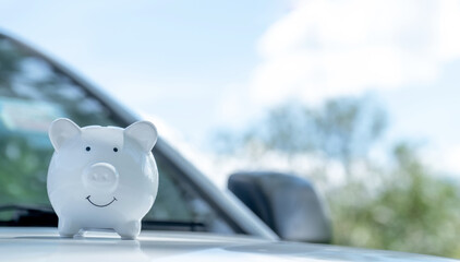 White piggy bank on the car, Money-saving concept for insurance, or traveling during retirement
