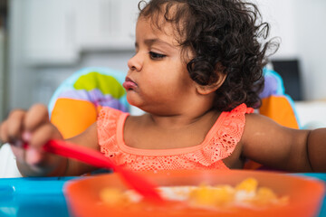 Profile picture of a brown skinned baby girl eating
