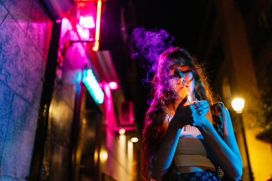 redhead woman lights a cigarette in the street at night