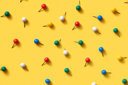 Office supplies pattern of multicolored pins on yellow.
