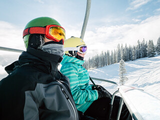 Tow teenagers on a chairlift on a sunny day in winter
